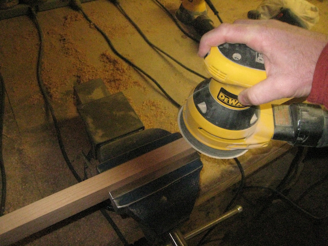 Sanding the edge of a piece of hard wood.