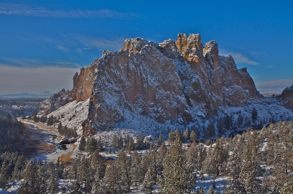 Smith Rock and the frozen Crooked River covered in snow.